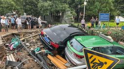Mobil-mobil yang rusak bertumpuk pada puing-puing setelah hujan lebat melanda kota Zhengzhou yang menyebabkan banjir di provinsi Henan, China tengah (21/7/2021). Luapan sungai menggenangi jalan-jalan dan membuat kendaraan terbawa arus setelah curah hujan 200 mm turun dalam satu jam. (AFP/STR)