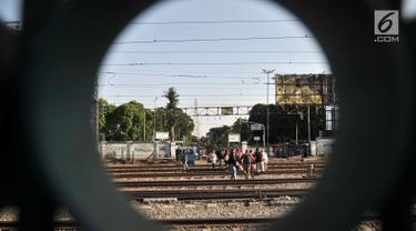 Warga menyeberangi perlintasan rel kereta api di kawasan Pisangan Baru, Jakarta, Selasa (10/9/2019). Mereka nekat menantang maut menyeberangi rel di dekat stasiun Jatinegara tersebut lantaran tidak adanya akses jembatan penyeberangan orang (JPO). (merdeka.com/Iqbal Nugroho)