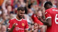 Duo gelandang Manchester United, Bruno Fernandes dan Paul Pogba, tampil gemilang saat bersua Leeds United pada laga pekan perdana Premier League di Old Trafford, Sabtu (14/8/2021) malam WIB. (AFP/Adrian Dennis)