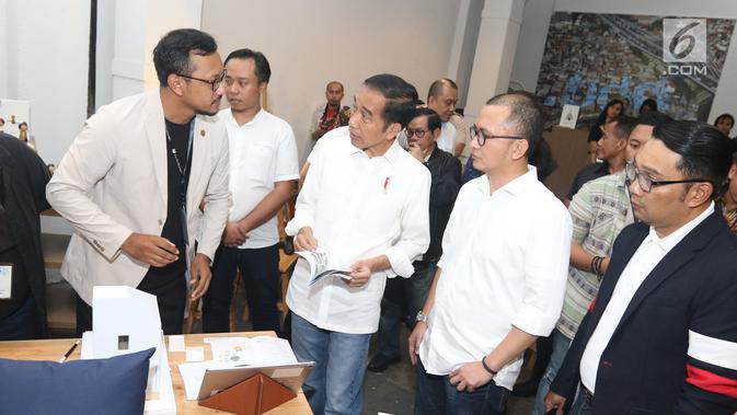 Calon Presiden Nomor Urut 01 Joko Widodo atau Jokowi menyimak penjelasan maket rumah sebelum berdiskusi dengan masyarakat kreatif Bandung di Simpul Space, Bandung, Jawa Barat,  Sabtu (10/11). (Liputan6.com/Angga Yuniar)
