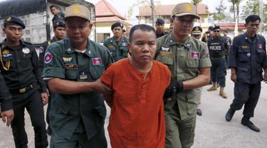 Yem Chrin (tengah) dikawal oleh petugas polisi saat tiba di Pengadilan Provinsi Battambang,Kamboja,Kamis (3/12). Pengadilan Kamboja menghukum Yem Chrin  25 tahun penjara dengan kasus pembunuhan dan penyebaran HIV lebih dari 270 orang. (REUTERS/Stringer)