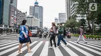 Pejalan kaki menyeberang jalan di kawasan Sudirman, Jakarta Pusat, Rabu (6/1/2021). Pemerintah memberlakukan kebijakan pembatasan sosial berskala besar (PSBB) di wilayah Jawa dan Bali mulai 11 hingga 25 Januari 2021 menyusul lonjakan kasus Covid-19 di sejumlah daerah. (Liputan6.com/Faizal Fanani)
