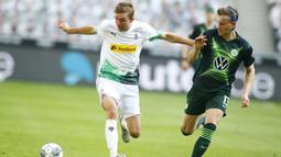 Gelandang Borussia Monchengladbach, Christoph Kramer, berebut bola dengan bek Wolfsburg, Yannick Gerhardt, pada laga lanjutan Bundesliga di Borussia Park Stadium, Rabu (17/6/2020) dini hari WIB. Monchengladbach menang telak 3-0 atas Wolfsburg.(AFP/Thilo Schmuelgen/pool)