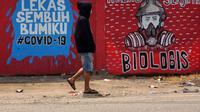 Seorang lelaki Indonesia yang mengenakan masker berjalan melewati mural di tengah kekhawatiran pandemi Virus Corona COVID-19 di Tangerang. (Fajrin Raharjo / AFP)