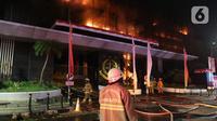 Petugas pemadam kebakaran berusaha memadamkan api yang membakar bagian gedung di Kompleks Kejaksaan Agung Republik Indonesia, Sabtu (22/8/2020). Upaya mempercepat pemadaman kebakaran dilakukan dengan menambah unit pemadam dari sebelumnya 5 menjadi 17 unit pemadam. (Liputan6.com/Herman Zakharia)