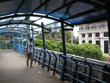 Pejalan kaki melintasi JPO yang atapnya rusak di kawasan Kuningan, Jakarta, Minggu (10/2). Kondisi JPO yang sebagian atapnya hilang tersebut mengganggu kenyamanan pejalan kaki, terutama saat hujan. (Liputan6.com/Immanuel Antonius)