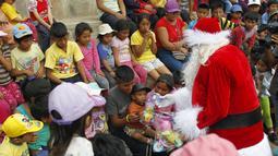 Seorang petugas polisi berpakaian seperti Santa Claus memberikan hadiah kepada anak-anak selama perayaan Natal di Huaycan, Lima, Peru (15/12/2015). (REUTERS/Janine Costa)