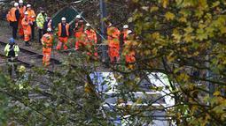 Petugas layanan darurat berkumpul di lokasi terbaliknya sebuah trem di sebuah terowongan di Croydon, London Selatan, Inggris, Rabu (9/11). Masinis trem telah diamankan dan tim penyelidik mulai mencari tahu penyebab kecelakaan. (REUTERS/Neil Hall)