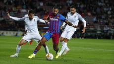 Penyerang Barcelona, Memphis Depay (tengah) mengontrol bola dibayangi pemain Granada pada lanjutan La Liga di Camp Nou, Selasa (21/9/2021) dini hari WIB. Barcelona dipaksa bermain imbang 1-1 oleh tamunya Granada. (AP Photo/Joan Monfort)