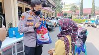 Kapolres Garut AKBP Wirdhanto Hadicaksono membagikan  paket bansos TNI-Polri bagi warga terdampak kebijakan Pemberlakukan Pembatasan Kegiatan Masyarakat (PPKM) Darurat Covid-19 di Garut. (Liputan6.com/Jayadi Supriadin)