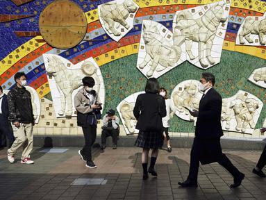 Orang-orang yang mengenakan masker pelindung untuk membantu mengekang penyebaran virus corona COVID-19 berjalan di Distrik Shibuya, Tokyo, Jepang, Rabu (7/4/2021). Tokyo mengonfirmasi lebih dari 550 kasus COVID-19 baru pada 7 April 2021. (AP Photo/Eugene Hoshiko)