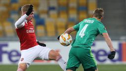 Pemain Arsenal, Emile Smith Rowe (kiri) berebut bola dengan Igor Perduta asal Vorskla Poltava saat bertanding pada laga kelima Grup E Liga Europa di Stadion NSK Olimpiyskiy, Kyiv, Ukraina, Jumat (30/11). Arsenal menang 3-0. (AP Photo/Efrem Lukatsky)