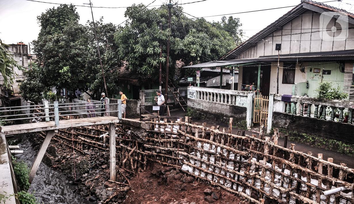 Warga mengamati turap kali yang longsor di Batu Ampar, Kramat Jati, Jakarta, Selasa (23/2/2021). Turap kali sepanjang 30 meter di permukiman RT 17 dan 13 RW 02 Kelurahan Batu Ampar longsor pada Sabtu (20/2) akibat derasnya arus air ketika aliran Kali Ciliwung meluap. (merdeka.com/Iqbal S. Nugroho)