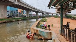 Anak-anak bermain dan berenang di Sungai Kalimalang, Jakarta Timur, Jumat (5/7/2019). Tingginya suhu udara Ibu Kota akibat musim kemarau menyebabkan anak-anak tersebut berenang di Sungai Kalimalang meski dengan kondisi seadanya. (Liputan6.com/Immanuel Antonius)