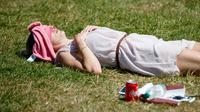 Seorang wanita Inggris berjemur di atas rumput sambil menikmati sinar matahari di Green Park, London, Senin (25/6). Pada Juli 2018, suhu di ibu kota London tercatat 29.1 derajat Celcius dan diprediksi akan mencapai 30 derajat Celcius. (AFP/Tolga Akmen)