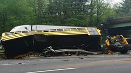 Kondisi bus sekolah yang terbalik setelah bertabrakan dengan truk sampah di Interstate 80, Mount Olive, New Jersey, Kamis (17/5). Bus membawa siswa kelas V East Brook Middle School di Paramus, menuju Waterloo untuk karyawisata. (Chrissy Oleszek via AP)