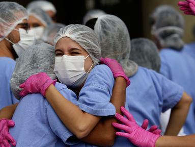 Petugas medis merayakan ketika tiga pasien terakhir meninggalkan rumah sakit lapangan di Stadion Nasional Mane Garrincha di Brasilia, Brasil, Kamis (15/10/2020). Para tenaga kesehatan berkumpul saat pasien COVID-19 terakhir pulang setelah dinyatakan sembuh. (AP Photo/Eraldo Peres)