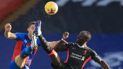 Striker Liverpool, Sadio Mane, berebut bola dengan bek Crystal Palace, Gary Cahill, pada laga lanjutan Liga Inggris di Selhurst Park Stadium, Sabtu (19/12/2020) malam WIB. Liverpool menang 7-0 atas Crystal Palace. (AFP/Adam Davy/pool)