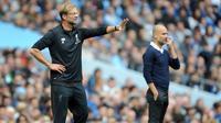 Pelatih Liverpool Juergen Klopp (kiri) dan disebelahnya pelatih Manchester City Pep Guardiola memberi arahan kepada timnya saat pertandingan Liga Inggris di Stadion Etihad, Manchester (9/9). (AP Photo/Rui Vieira)
