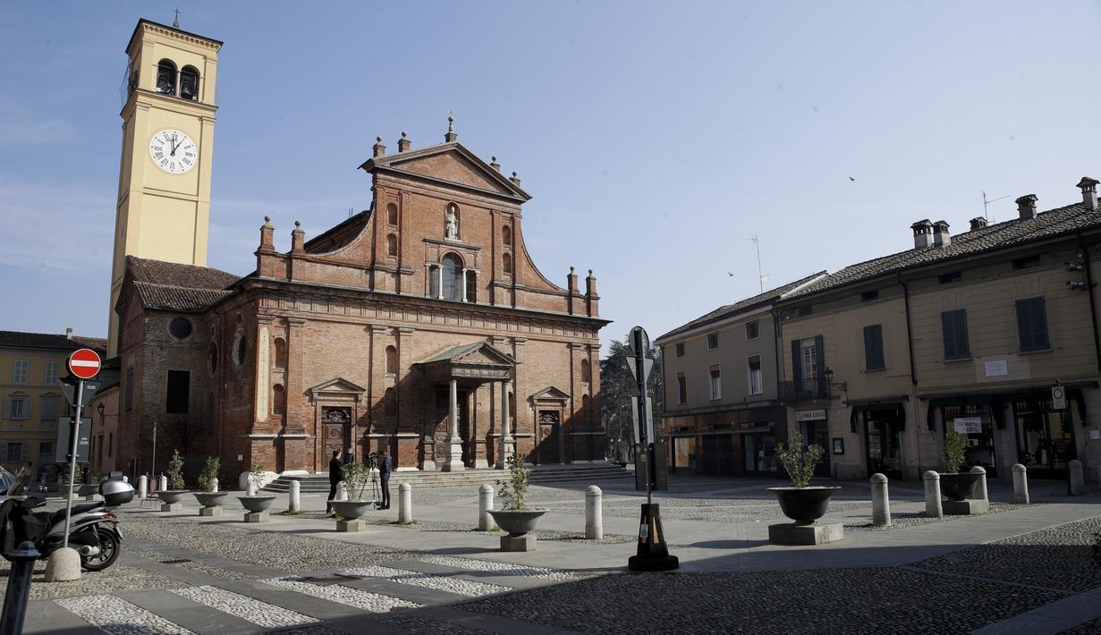 Dua jurnalis berdiri di depan Gereja San Biagio di Codogno, dekat Lodi, Italia Utara, Sabtu, (22/2/2020). Pihak berwenang Italia memerintahkan penutupan sekolah, bar, dan ruang publik lainnya di 12 kota, menyusul banyaknya kasus virus corona baru muncul di negara itu. (AP Photo/Luca Bruno)