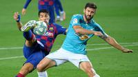 Striker Barcelona, Luis Suarez, berebut bola dengan bek Osasuna, Raul Navas, pada laga lanjutan La Liga pekan ke-37 di Camp Nou, Jumat (17/7/2020) dini hari WIB. Barcelona kalah 1-2 atas Osasuna. (AFP/Lluis Gene)