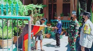 Petugas Kepolisian dan TNI melakukan penurunan bendera sasing yang dipasang oleh warga Kota Gorontalo (Arfandi Ibtahim/Liputan6.com)