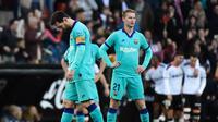 Pemain Barcelona, Lionel Messi dan Frenkie de Jong, terlihat lemas saat Valencia berhasil mencetak gol ke gawang Barcelona. Valencia menang 2-0 atas Barcelona di Mestalla, dalam laga jornada 21 La Liga, Sabtu (25/1/2020). (Jose Jordan/AFP)