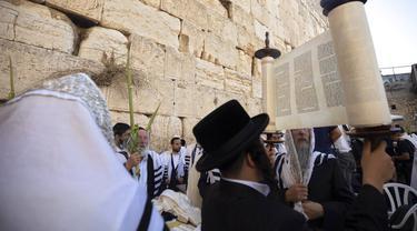 Pria Yahudi Ultra-Ortodoks berdoa selama hari raya Yahudi Sukkot di Tembok Barat, situs paling suci di mana orang Yahudi dapat berdoa di Kota Tua Yerusalem, Rabu (22/9/2021).  (AP Photo/Sebastian Scheiner)