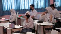 Siswa mengikuti uji coba pembelajaran tatap muka (PTM) terbatas di SMAN 1 Kota Tangerang, Banten, Senin (6/9/2021). Dinas Pendidikan Provinsi Banten uji coba PTM di SMA di Kota Tangerang secara terbatas dengan sistem bergiliran serta menerapkan protokol kesehatan ketat. (Liputan6.com/Angga Yuniar)