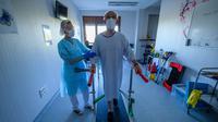 Fisioterapis merawat pasien yang sedang menjalani proses rehabilitasi setelah sembuh dari infeksi virus corona COVID-19 di sebuah rumah sakit di Illkirch-Graffenstaden, Prancis, Selasa (14/4/2020). Prancis memperpanjang lockdown karena dinilai ampuh menahan kasus baru COVID-19. (PATRICK HERTZOG/AFP)