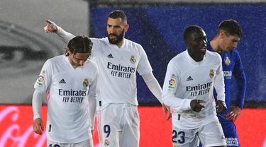 Striker Real Madrid, Karim Benzema (tengah) melakukan selebrasi usai mencetak gol pertama timnya ke gawang Getafe dalam laga lanjutan Liga Spanyol 2020/21 pekan ke-22 di Alfredo di Stefano Stadium, Selasa (9/2/2021). Real Madrid menang 2-0 atas Getafe. (AFP/Gabriel Bouys)