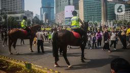 Sejumlah warga berfoto dengan polisi berkuda dari Direktorat Polisi Satwa Mabes Polri di kawasan Bundaran HI, Jakarta, Minggu (17/11/2019). Polisi berkuda tersebut khusus ditugaskan mengawasi keamanan CFD serta memperkenalkan kepada warga. (Liputan6.com/Faizal Fanani)