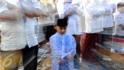Ribuan umat muslim menunaikan ibadah salat Idul Fitri 1 Syawal 1436 H di Masjid Agung Al Azhar Jakarta, Jumat (17/7/2015). Tampak, salah satu anak terlihat khusyuk saat melaksanakan salat Id di halaman Masjid Agung Al Azhar. (Liputan6.com/Yoppy Renato)