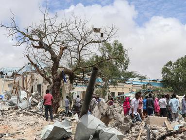 Warga Somalia berkumpul di lokasi ledakan bom mobil di luar kantor pemerintah lokal di Mogadishu, Somalia, (10/9). Menurut polisi Somalia dan pekerja penyelamat, enam orang tewas dan 16 luka-luka akibat ledakan tersebut. (AFP Photo/Abdi Haji Hussein)