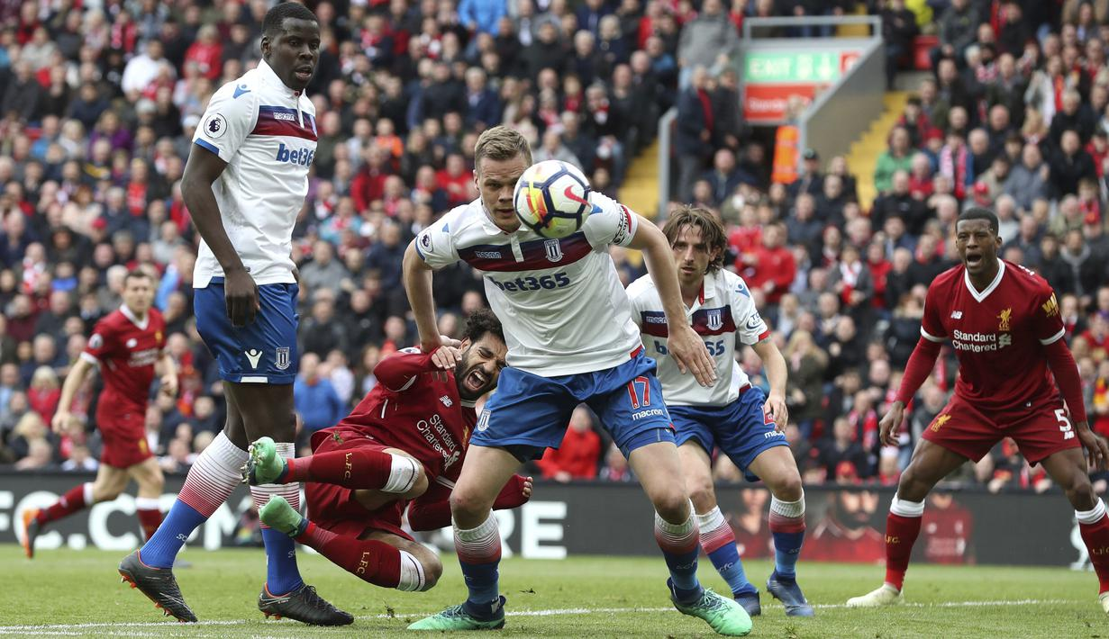 Pemain Liverpool, Mohamed Salah jatuh saat berebut bola dengan pemain Stoke city pada lanjutan Premier League di Anfield, Liverpool, (28/4/2018). Liverpool hanya bermain imbang 0-0 melawan Stoke City. (Martin Rickett/PA via AP)