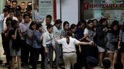 Para sandera berjalan keluar saat dibebaskan dalam penyanderaan di V-Mall, Manila, Filipina, Senin (2/3/2020). Pelaku penyenderaan Alchie Paray menyerahkan diri setelah membebaskan 30 sandera. (AP Photo/Aaron Favila)