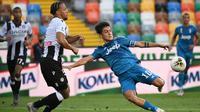 Penyerang Juventus,  Paulo Dybala menendang bola dari kawalan bek Udinese, William Troost-Ekong pada pertandingan lanjutan Liga Serie A Italia di Stadion Dacia Arena di Udine (23/7/2020). Udinese menang 2-1 atas Juventus. (AFP Photo/Marco Bertorello)