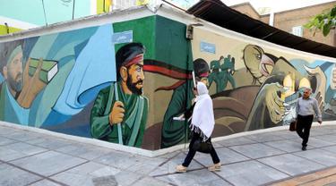 Pejalan kaki melewati lukisan mural yang menggambarkan para prajurit Iran di Palestine Square, Ibu Kota Teheran, Iran, Sabtu (22/6/2019). (ATTA KENARE/AFP)