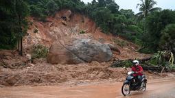 Pengendara motor melihat sebuah batu besar usai tanah longsor di Paung, negara bagian Mon (9/8/2019). Tanah longsor yang disebabkan oleh hujan lebat menewaskan sedikitnya 13 orang dan melukai puluhan lainnya di Myanmar timur. (AFP Photo/Ye Aung Thu)