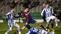 Pedri Barcelona, tengah, bertarung memperebutkan bola dengan bek Real Sociedad dalam pertandingan semifinal Piala Super Spanyol di stadion Nuevo Arcangel di Cordoba, Spanyol, Rabu, 13 Januari 2021. (Foto AP / Jose Breton)