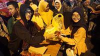 Seorang pengunjung sedang menukarkan sampah hasil pungutan di lokasi wisata lampion Pasar Gede dengan kue keranjang, Rabu malam (22/1).(Liputan6.com/Fajar Abrori)