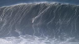 Peselancar asal Portugal, Joao Guedes beraksi saat menaklukan ombak selama sesi surfing ombak besar di Praia do Norte di Nazare, Portugal tengah (13/1). (AP Photo / Armando Franca)