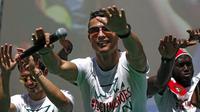 Cristiano Ronaldo dan tim kesebelasan menyapa pendukung mereka di atas bus terbuka saat kembali ke Lisbon, Portugal, Senin (11/7). Portugal menjadi juara Piala Eropa 2016 usai mengalahkan Prancis di final. (REUTERS / Pedro Nunes)