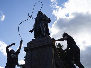 Mike Forcia (kiri) dan seorang pria mengikatkan tali pada leher patung Christopher Columbus saat sekelompok massa merobohkannya di Minnesota State Capitol, St. Paul, Minnesota, Amerika Serikat, Rabu (10/6/2020). (Evan Frost/Minnesota Public Radio via AP)
