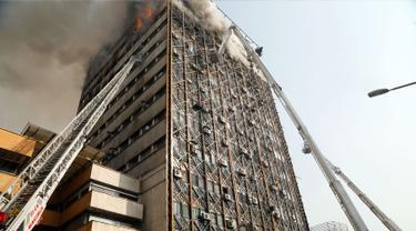 Petugas pemadam menggunakan crane mobil damkar untuk memadamkan kebakaran gedung tertua Iran, gedung Plasco, di pusat kota Teheran, Kamis (19/1). Sedikitnya 38 orang terluka akibat kebakaran di Gedung Plasco yang ikonik tersebut. (AFP PHOTO/STR)