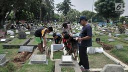 Anak-anak membersihkan makam di TPU Cipinang Baru, Jakarta, Minggu (5/5/2019).  Anak-anak yang mayoritas masih duduk di sekolah dasar ini biasanya melayani jasa Ngoret secara berkelompok dengan tugas masing-masing seperti menyapu dan membersihkan sekitar makam. (merdeka.com/Iqbal S. Nugroho)