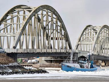 Sebuah kapal nelayan menabrak Jembatan Anggersudn di perairan dingin di Limfjord di bagian utara Jutland di Denmark (28/2).  Tiga awak kapal berhasil diselamatkan sebuah helikopter atas kejadian tersebut. (AFP Photo/Scanpic Denmark/Henning Bagger)