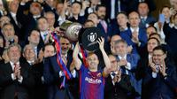 Kapten Barcelona, Andres Iniesta mengangkat trofi Copa del Rey setelah memenangkan pertandingan melawan Sevilla pada babak final di stadion Wanda Metropolitano di Madrid, Spanyol (21/4). Barcelona menang telak 5-0.  (AP Photo / Paul White)