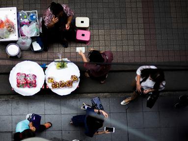 Pedagang buah-buahan melayani pelanggan di Bangkok, Thailand (20/9). Bangkok dikenal punya sejarah panjang sebagai pusat makanan jalanan di dunia. (AFP Photo/Jewel Samad)