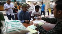 Seorang pria saat membayarkan zakat fitrah pada panitia amil zakat di Masjid Istiqlal, Jakarta, Jumat (1/7). Waktu pembayaran zakat fitrah dibuka hingga malam takbiran. (Liputan6.com/Faizal Fanani)